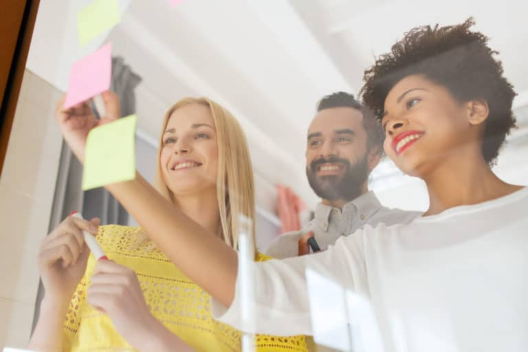 Entrepreneurs en train de coller des post-it sur la vitre d'un bureau